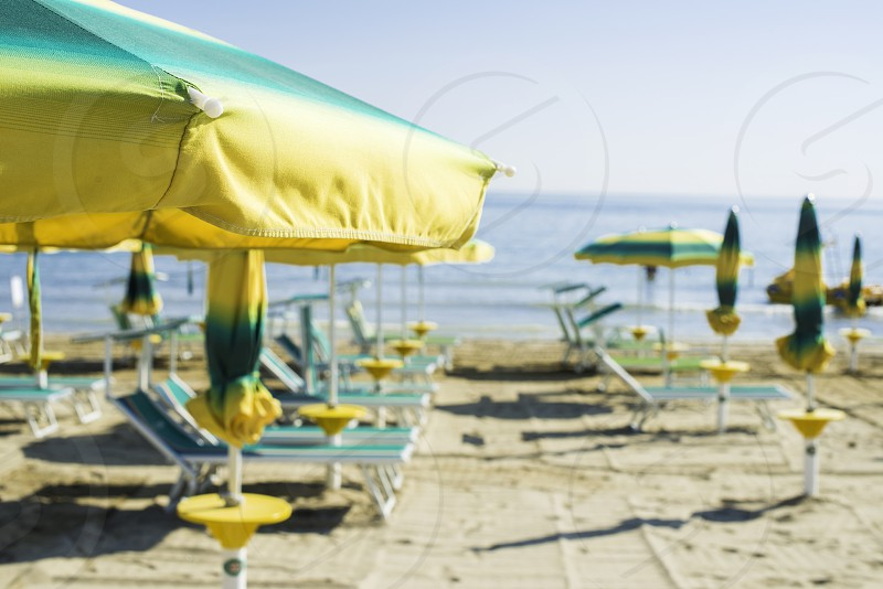 Green sunbeds and umbrellas on the beach. photo