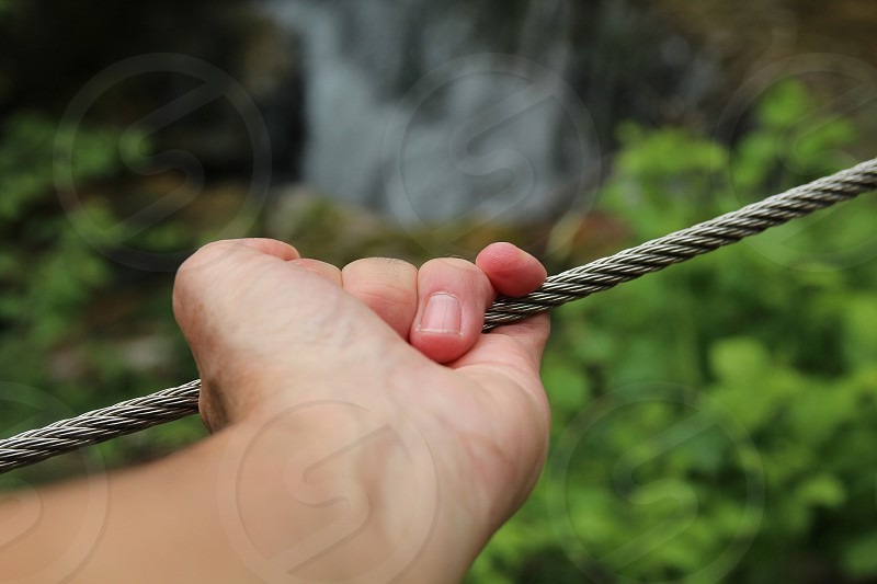 hand on metal cable photo