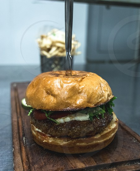 close up photography of hamburger with a stainless steel knife on top photo