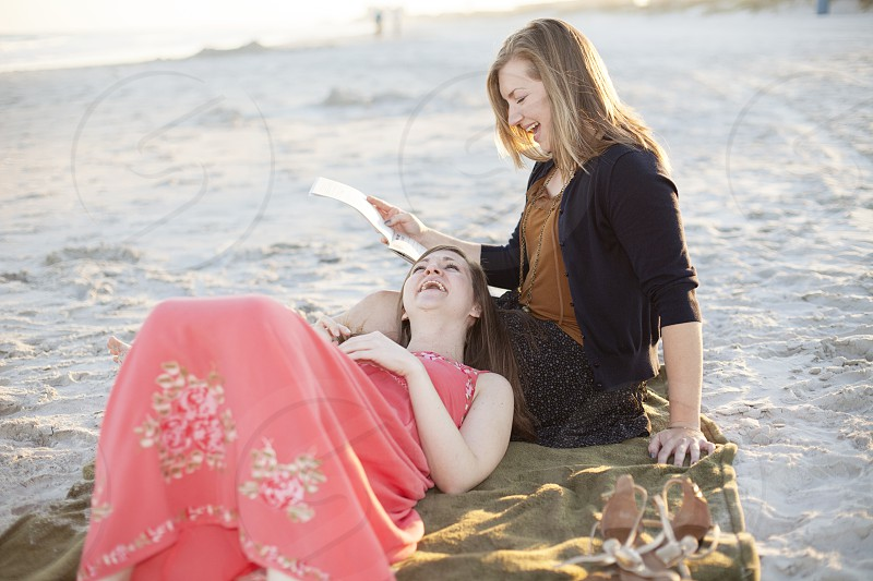 woman in black cardigan sitting on brown blanket on white sand while woman in pink floral dress lying on her lap photo