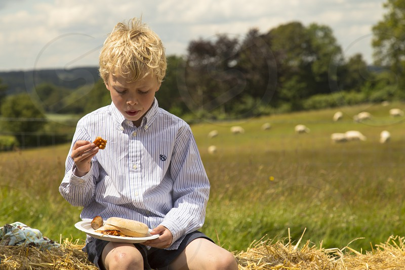 boy in blue and white dress shirt holding a plate with foods while sitting on the grass photo