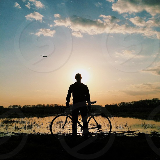 man standing near lake with bike photo