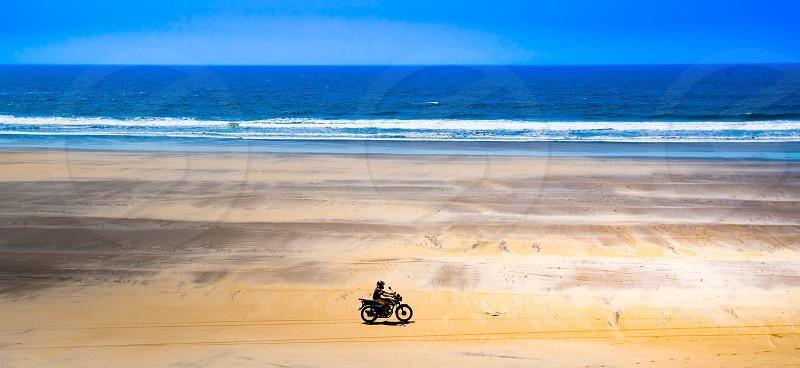 Motorcycle adventure beach ocean daredevil fun escape waves blue motorcycle rider tourism exotic fun uplifting photo