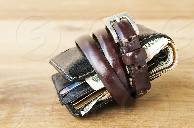 Wallet tied with a belt on wooden table. photo