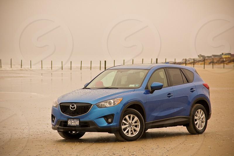blue Mazda SUV on seashore at daytime photo