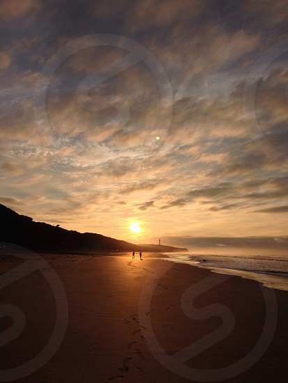 2 person walking with background sunset photo