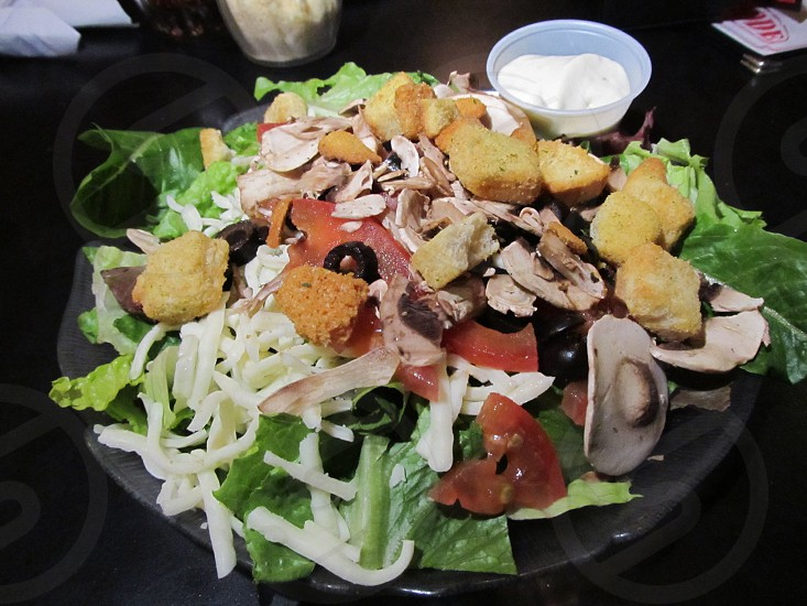 Individual salad with mushrooms croutons tomatoes black olives and cheese photo