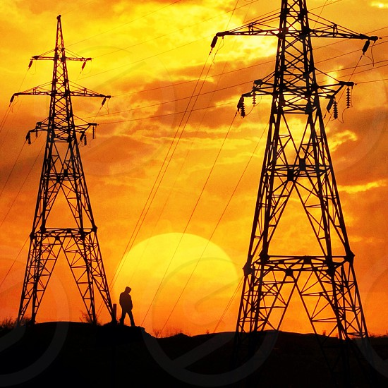 human finger standing by power towers by orange setting sun sky photo