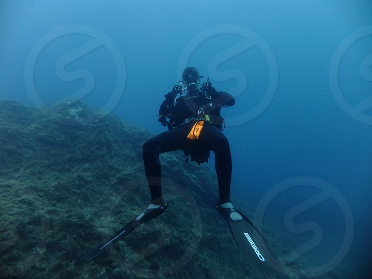 person scuba diving on sea taking photo photo