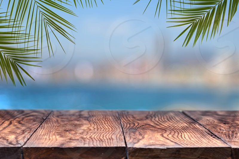 wooden table or wooden mock up with palm trees against the background of a blurry city . Natural background with copy space. Can be used for display products. photo