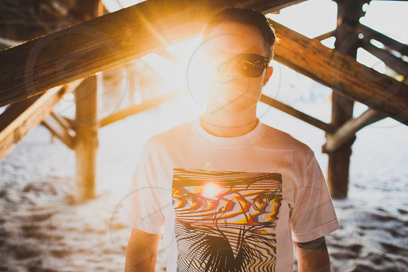 man wearing a white graphic t shirt and sunglasses photo