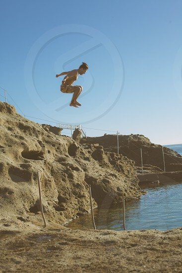 woman in bikini jumping off a cliff into clear water photo