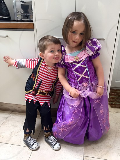 boy  in a pirate costume beside a girl with a princess costume standing near white cabinet photo