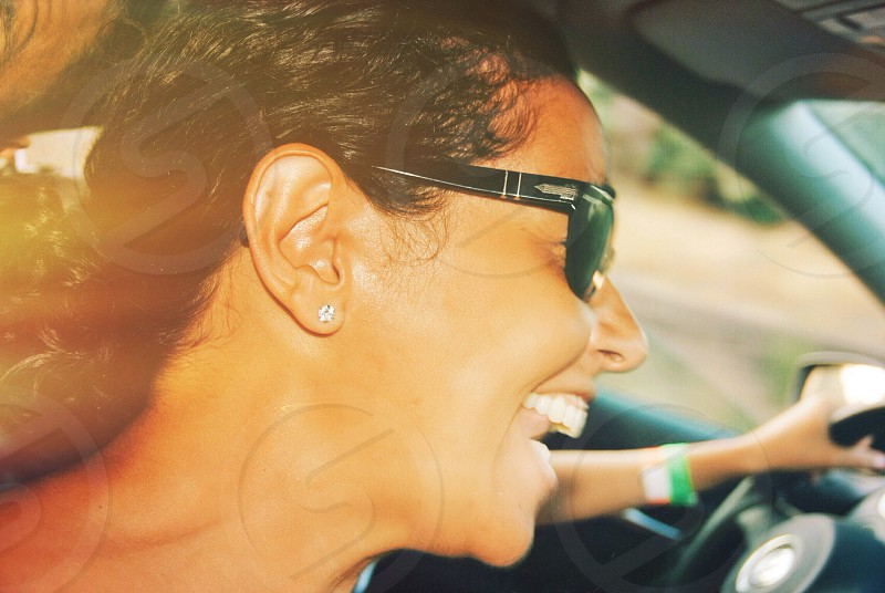 woman smiling wearing black and silver framed sunglasses photo