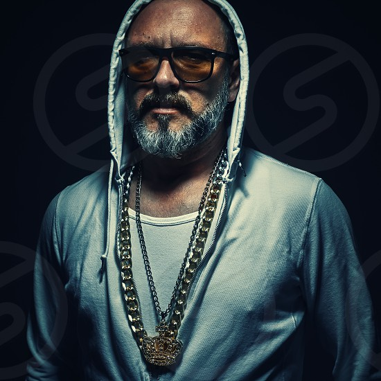 Portrait of an older street gangster middle aged man wearing tracksuit and golden jewelry.  photo