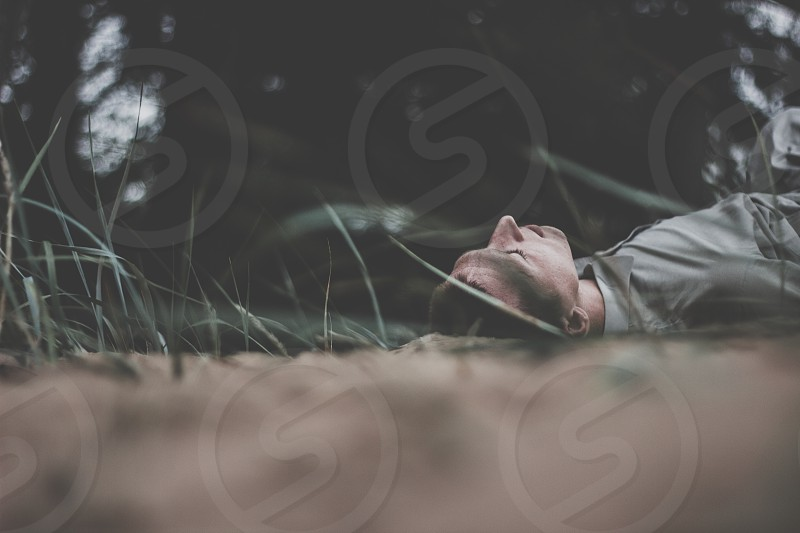 A man lies on his back in the forest relaxes and meditates. Savasana yoga pose photo