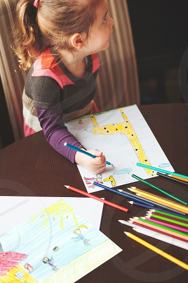 Little girl drawing a colorful pictures of giraffe and playing children using pencil crayons sitting at table indoors. Shot from above photo