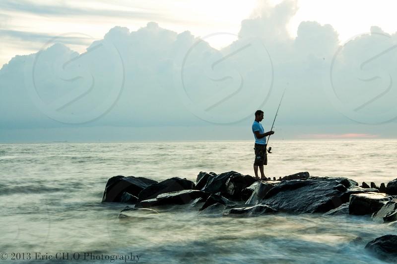 man holding fishing rod while standing on rocks near sea photo