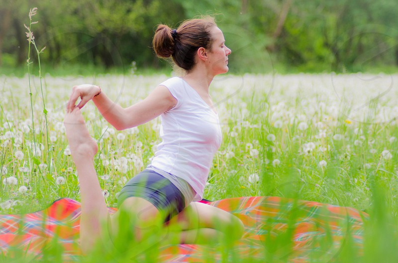 woman exercising at the dandelions field photo