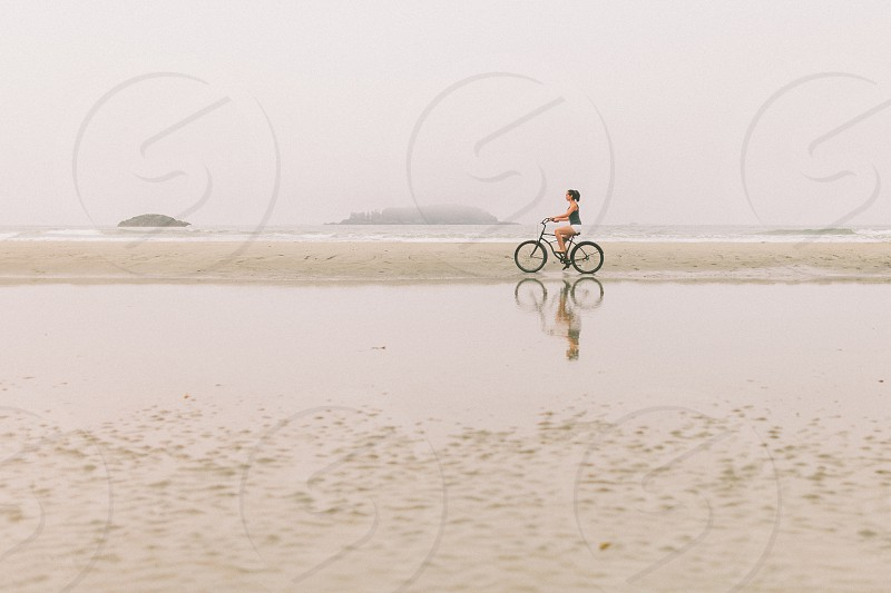 A woman riding a bike on the beach with her reflection cast in the water.  photo