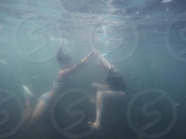 2 women swimming under water holding hands photo