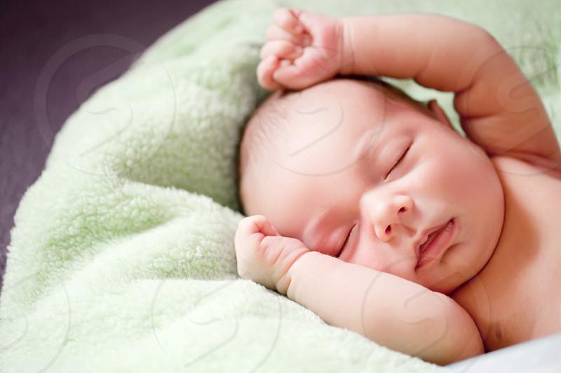 baby sleeping on green blanket photo