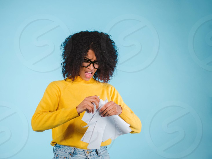 Breaking contract. Furious young african american woman with afro hairstyle tearing up paper on blue background. photo