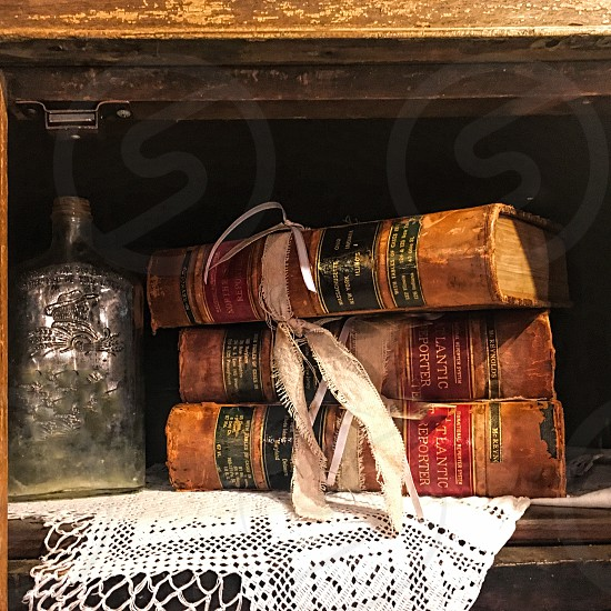 A set of vintage books are on a shelf on a doily photo