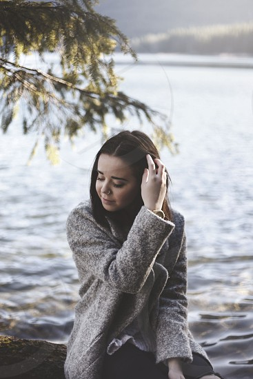 woman wearing grey sweater sitting while fixing her hair and lake behind photo