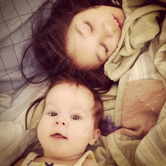 brunette girl sleeping next to brunette baby photo