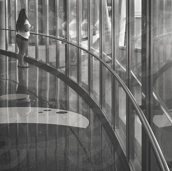 woman leaning on window glass greyscale photo