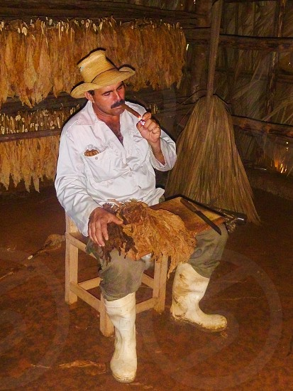 man in brown sombrero and white dress shirt and grey jeans sitting on brown wooden chair smoking tobacco photo