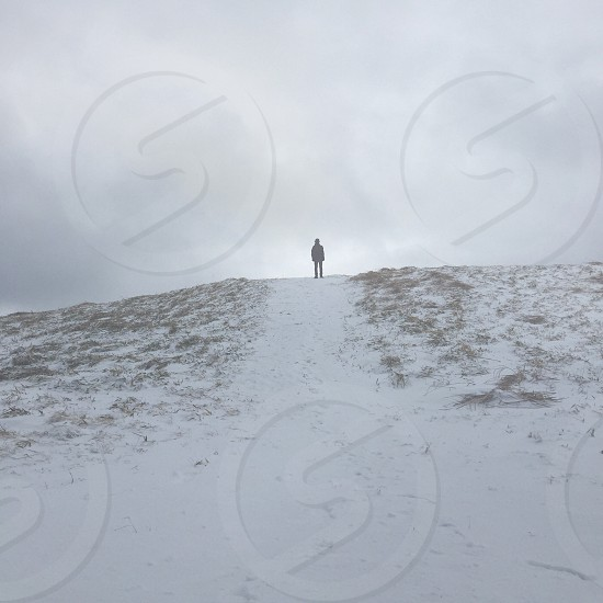 man standing on top of the hill photo