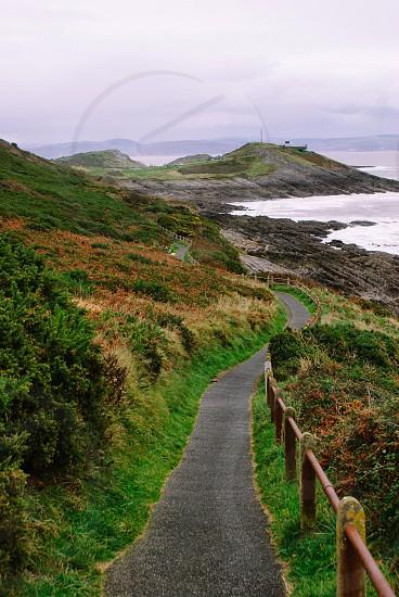 Wales United Kingdom Europe coast Atlantic Ocean sea shoreline green path way cape grass rock railing bush countryside route photo