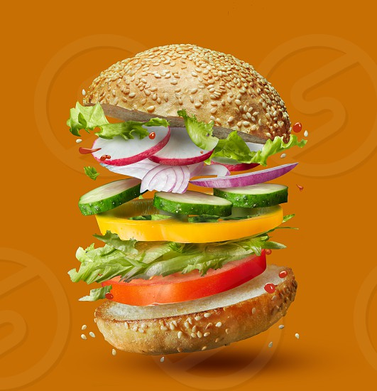 Burger preparation ingredients falling into place isolated on orange photo