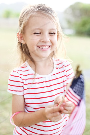 girl in white and red pinstriped t shirt holding american flaglet photo