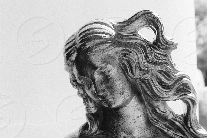 grayscale photo of woman metal statue with white wall paint behind photo