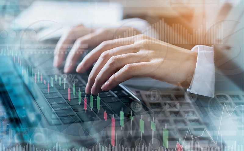 Double exposure of hand businessman using computer laptop and financial graph on building background stock market financial concept. photo