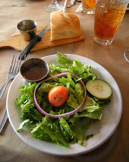Salad with onion and tomato with bread butter and iced tea photo
