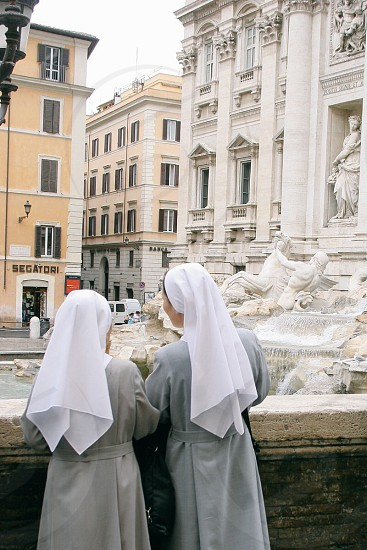 two nuns leaning on gray concrete balcony photo