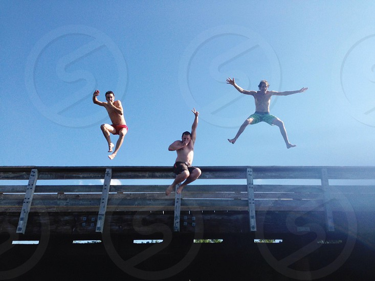 three man jumping off the bridge photo