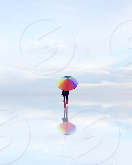 person in black coat holding yellow pink orange brown purple blue green and white umbrella walking on ice during daytime photo