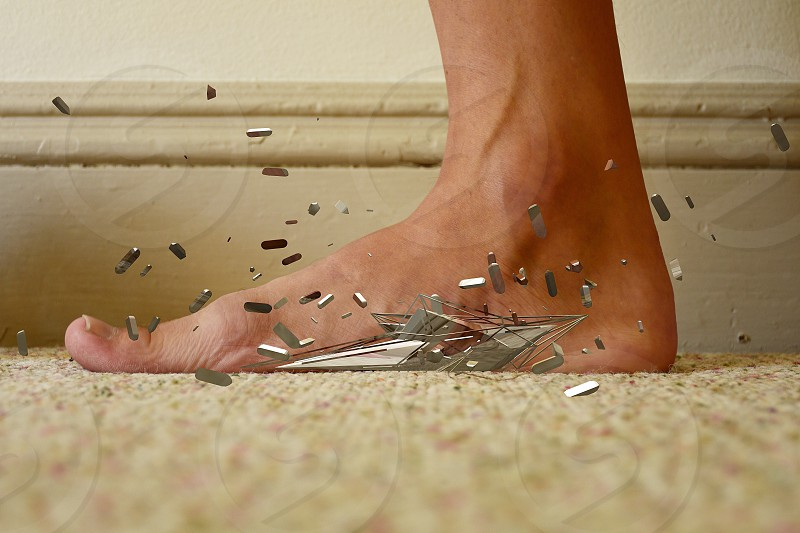 person's foot stepping onto a grey material blown to pieces photo