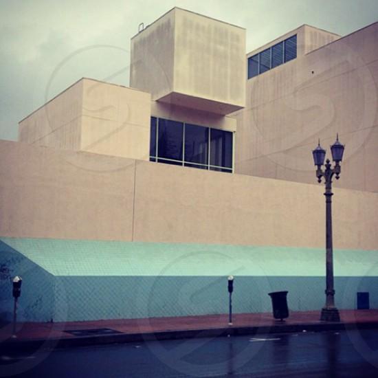 beige wall paint building and black light street bollard photo