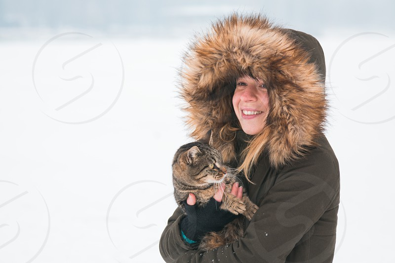 Young woman outside in the winter holding a cat photo