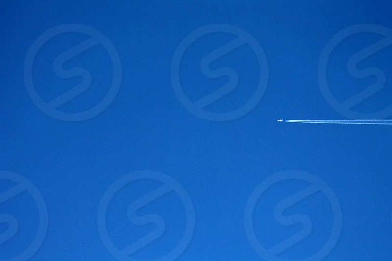 airplane skimming across the sky in the perfect blue summer sky  photo