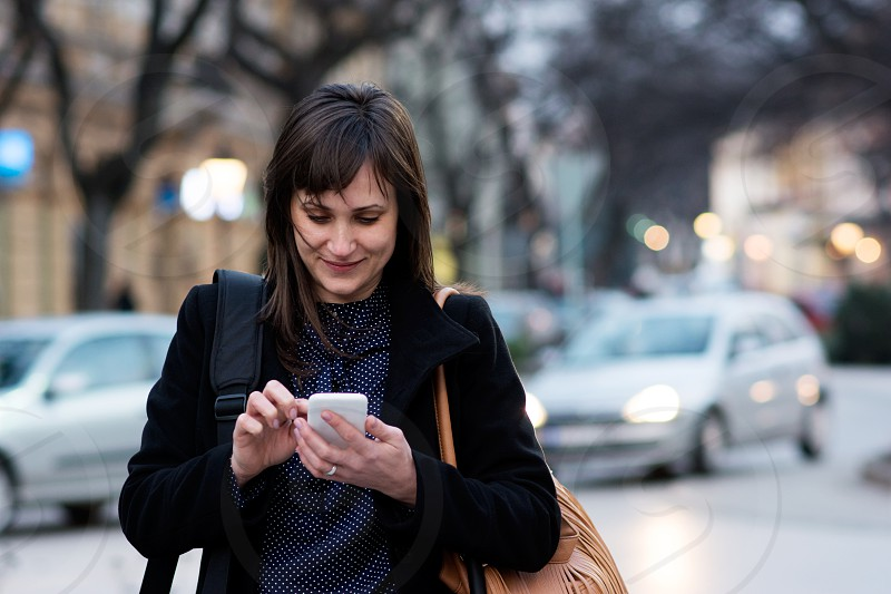 Woman browsing on her smartphone in the city center photo