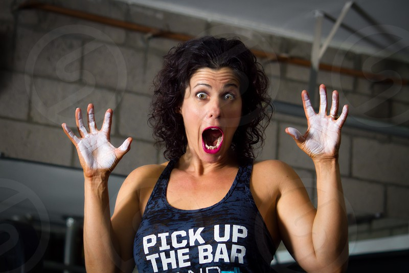 A weight lifting trainer feigns surprise as she holds up chalky hands. photo