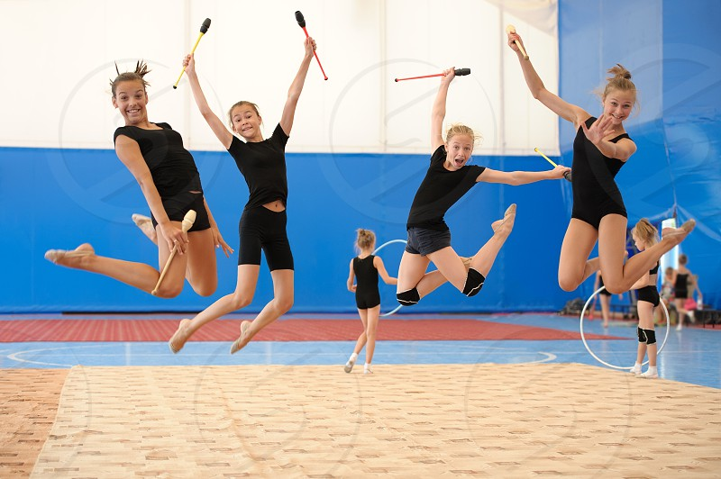 Group of four young female gymnasts posing with Indian clubs in a high jump photo
