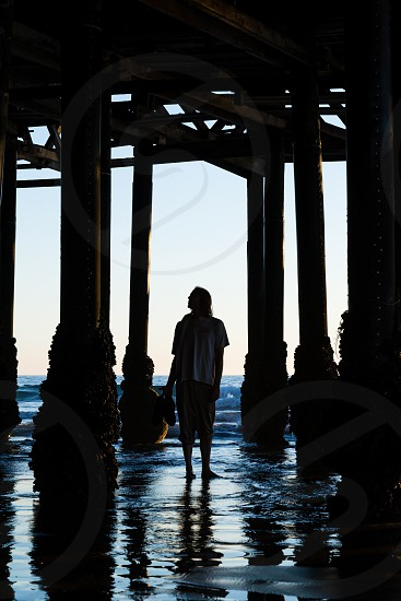 Reflective man under pier at sunset photo